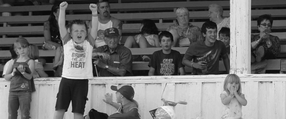 A boy raises his hands in excitement while watching an event